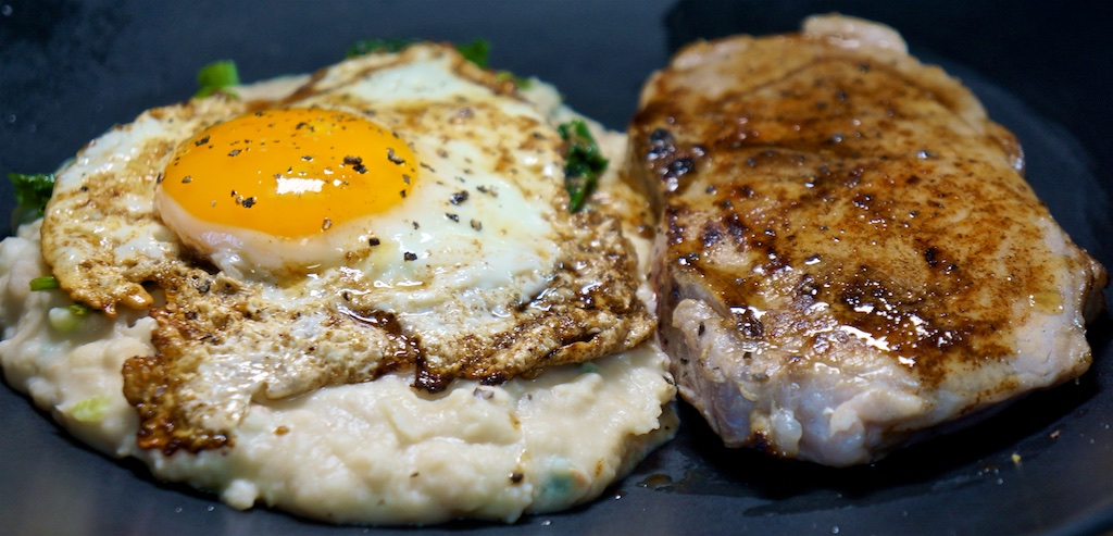 May 25: Cheese & Tomato on an Onion Bagel; Seared Pork Loin Chops; Mashed White Beans with Kale, Parmesan, and a Fried Egg